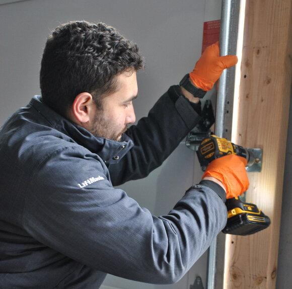 Installer drilling in garage door track